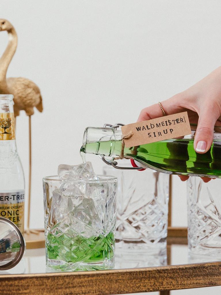 Selbst gemachter Waldmeistersirup wird fuer das Waldmeister Gin Tonic nach dem Rezept von Sweets & Lifestyle® in das Glas gegossen