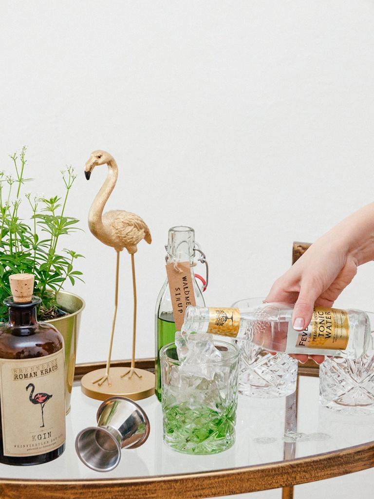 Foodbloggerin Verena Pelikan bei der Zubereitung von einem Waldmeister Gin Tonic in ihrem Kochstudio SchlossStudio im Weinviertel