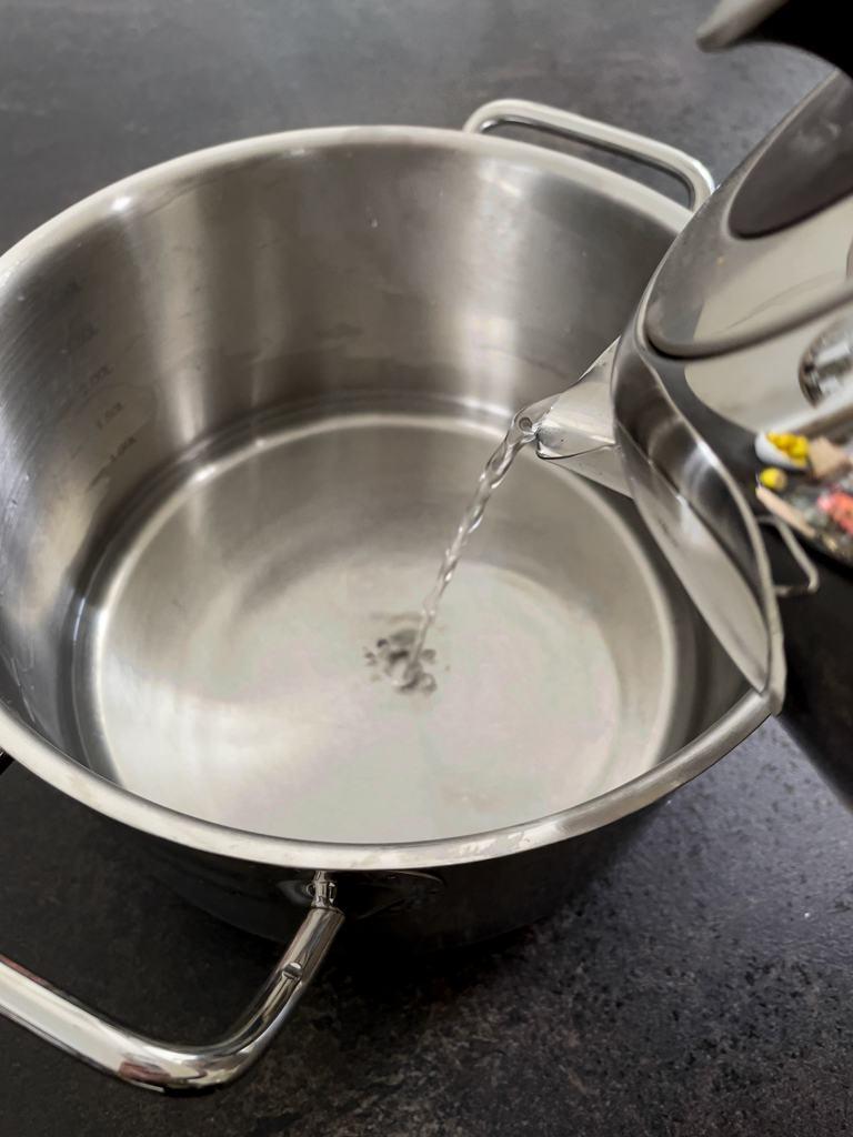 Heisses Wasser in einen grossen Topf leeren um das Bienenwachs und das Kokosfett fuer die Citronella Kerze zu schmelzen