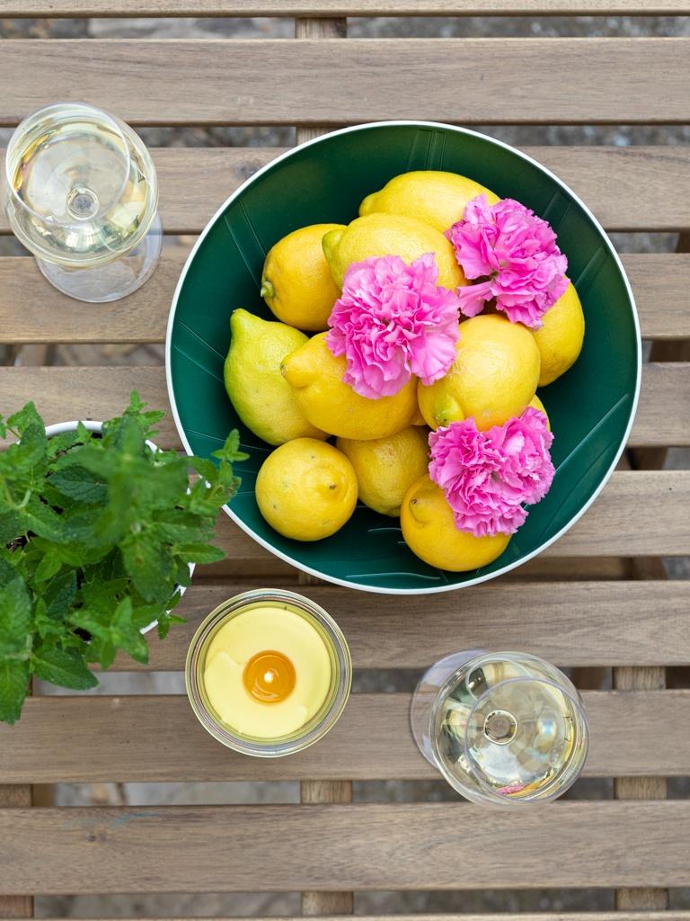 Selbst gemachte Citronella Kerze am Tisch mit frischen Zitronen und SchlossStudio Muskateller Frizzante