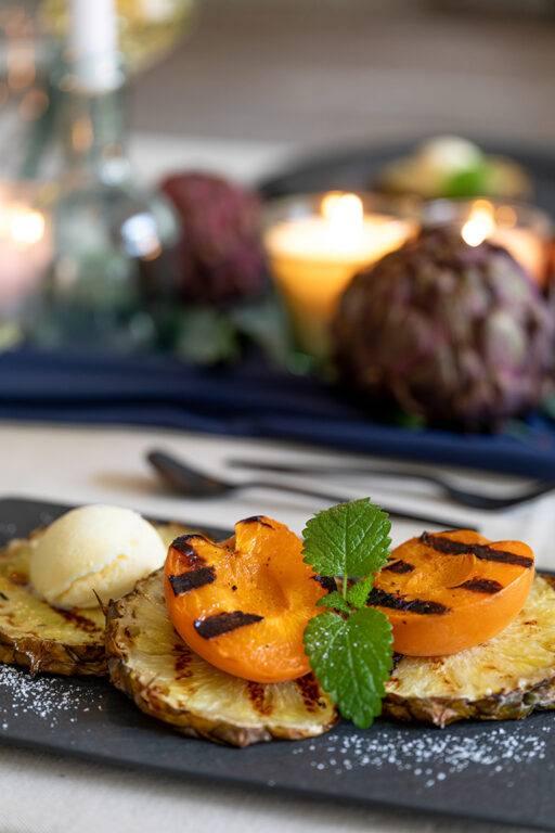 Gegrillte Marille auf gegrillter Ananas serviert mit einer Kugel Vanilleeis als Dessert bei der Grillparty nach einem Rezept von Sweets & Lifestyle®