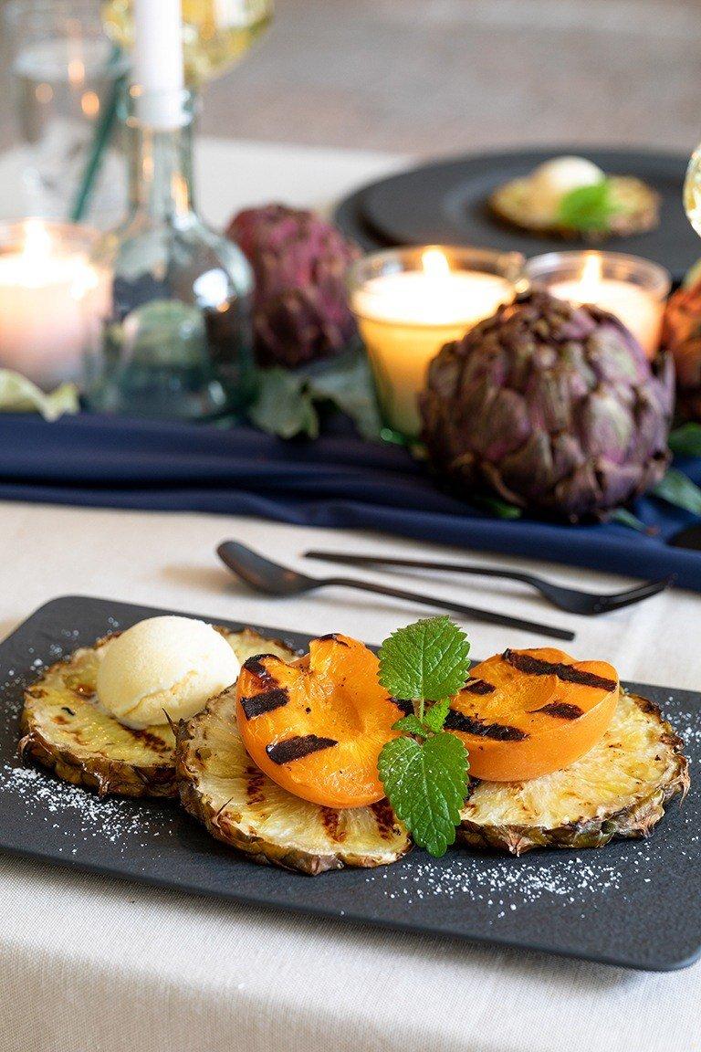 Gegrillte Marille serviert mit gegrillter Ananas und einer Kugel Vanilleeis als Dessert beim Grillen nach einem Rezept von Sweets & Lifestyle®