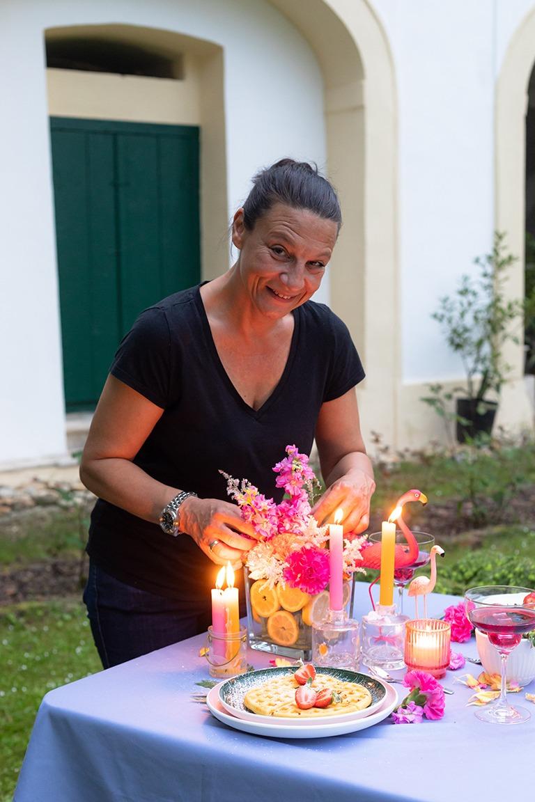 Dekoprofi Manuela Simek von mycelebration beim Dekorieren der Flamingo Party im Garten vom Kochstudio SchlossStudio von Verena Pelikan im Weinviertel