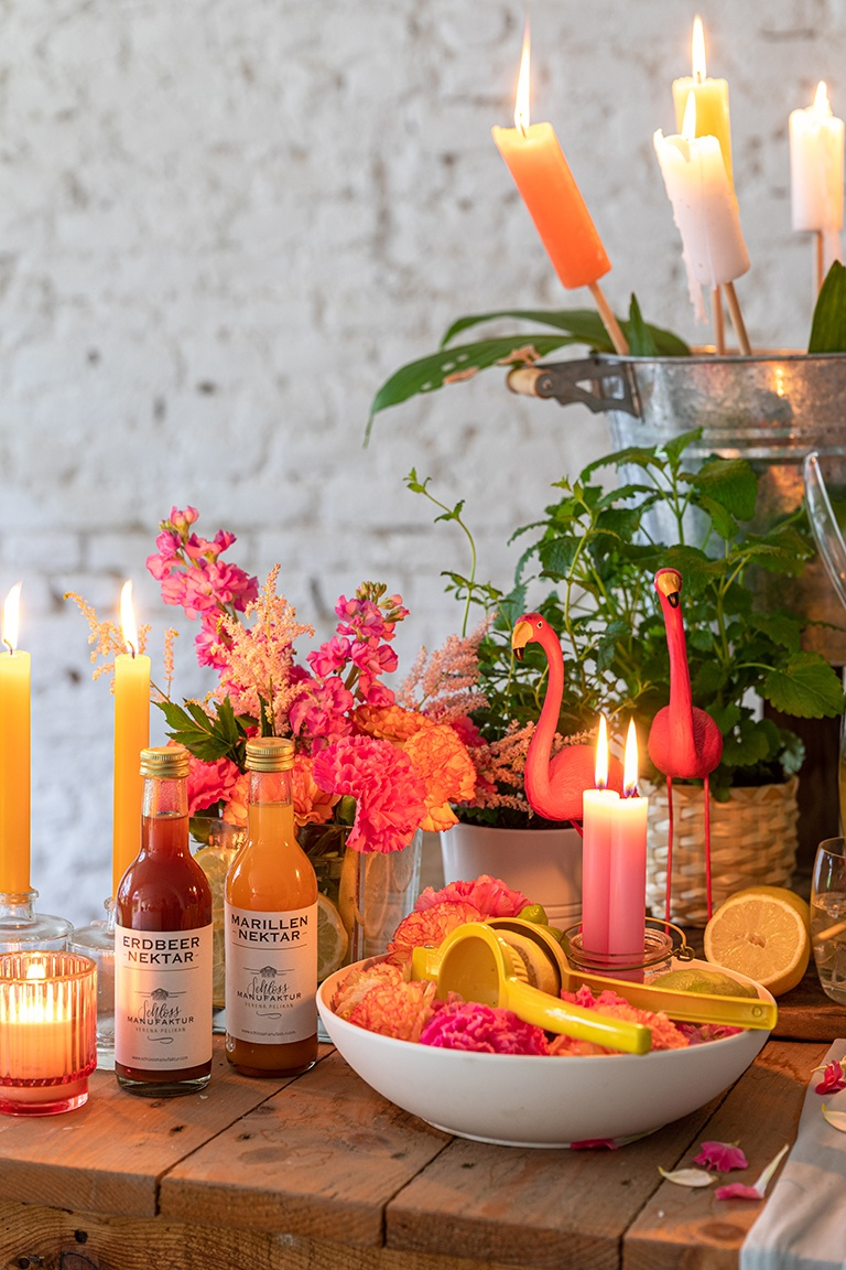 Farbenfrohe Blumendeko und Flamingos auf der Getraenkebar bei der Sommerparty im Kochstudio SchlossStudio von Verena Pelikan im Weinviertel