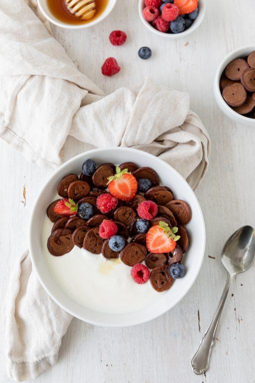 Kakao Mini Pancakes als Fruehstueck mit Joghurt und frischen Beeren serviert nach einem Rezept von Sweets & Lifestyle®
