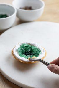 Brauner Kandiszucker wird von Verena Pelikan am Rand der Cookies auf dem Royal Icing platziert