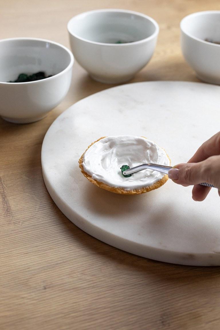 Eingefaerbter Kandiszucker wird von Verena Pelikan auf das Royal Icing gelegt um funkelnde Geode Cookies zu erhalten
