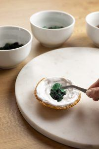 Verschieden intensiv eingefaerbter Kandiszucker wird auf die Royal Icing Schicht gelegt um huebsche Edelstein Cookies zu erhalten