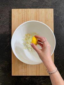 Zitronensaft wird zu den Zwiebelstuecken und Knoblauchstuecken hinzugegeben fuer die Zubereitung der Spaghetti Wurst Mumien nach einem Rezept von Sweets & Lifestyle®